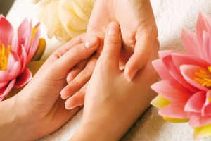 Hand massage being performed on client to relieve ailments